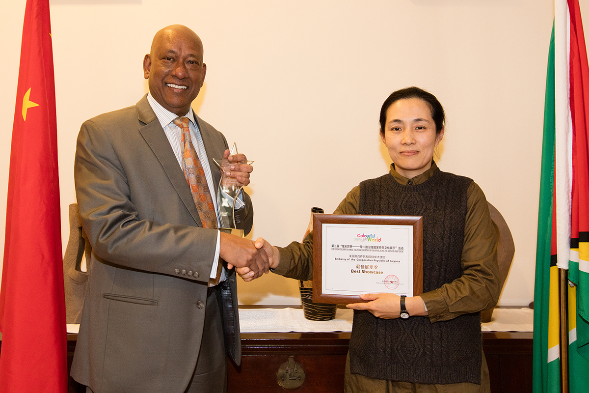 Ambassador Karran receiving the trophy and certificate from Ms Bingtao Zhang, Director of the Beijing Foreign Cultural Exchange Centre